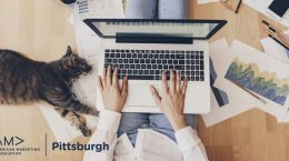 woman working from home with her cat laying beside her