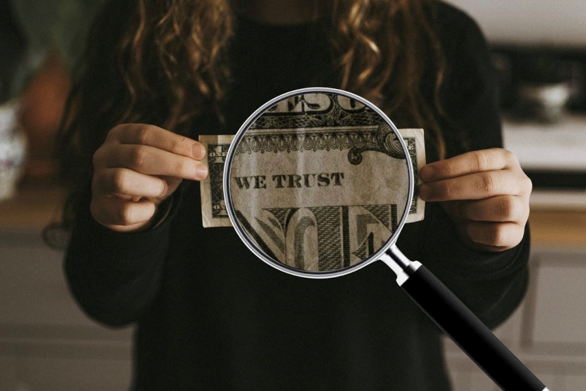 dollar bill under a magifying glass showing the We Trust text on the dollar bill.